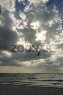 Crepuscular Rays Trough the Clouds on a Sandy Beach on the Caribbean Sea