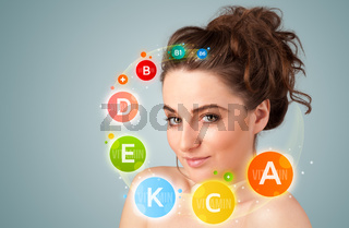 Pretty young girl with colorful vitamin icons and symbols