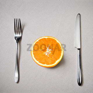 Healthy breakfast - fresh orange with knife and fork