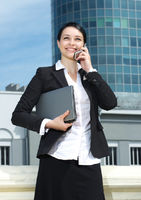 Cute young business lady talking mobile