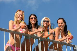 Beautiful women in bikinis smiling with drinks