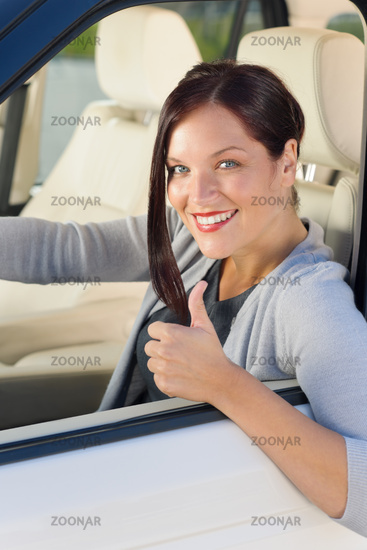 Attractive businesswoman in luxury car thumb-up