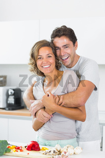 Husband hugging wife at the chopping board