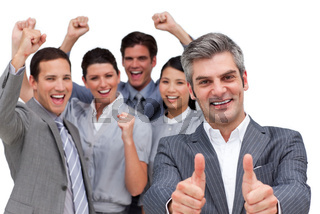 Happy manager with thumbs up standing with his team against a white background