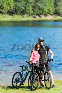 Teenager bikers hugging at lakeside