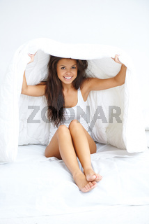 Young woman hiding under the bedclothes