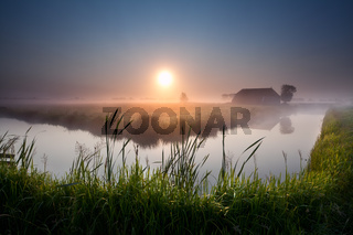 misty sunrise over river in farmland