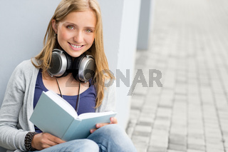 Woman reading book outside of school young