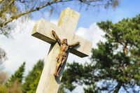 obliquely standing grave cross with Jesus figurine