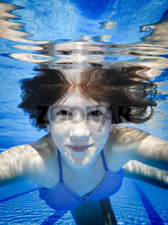 Teenage swimming underwater in the pool