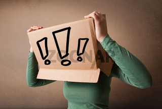 Young lady gesturing with a cardboard box on her head with exclamation point