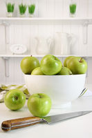 Green apples in bowl on table in kitchen
