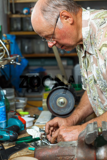 Senior working in workshop with different tools