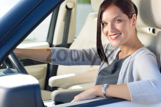 Attractive businesswoman drive luxury car smiling