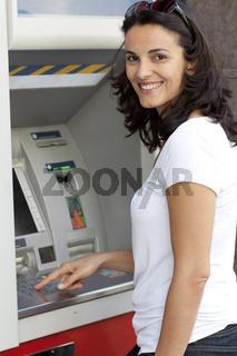 Frau gibt Geheimzahl am Geldautomaten ein