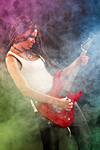 Fashion girl with guitar playing hard-rock. Coloured fog and light