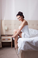 Smiling brunette sitting on hotel bed