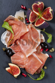 Tapas with prosciutto on a black plate