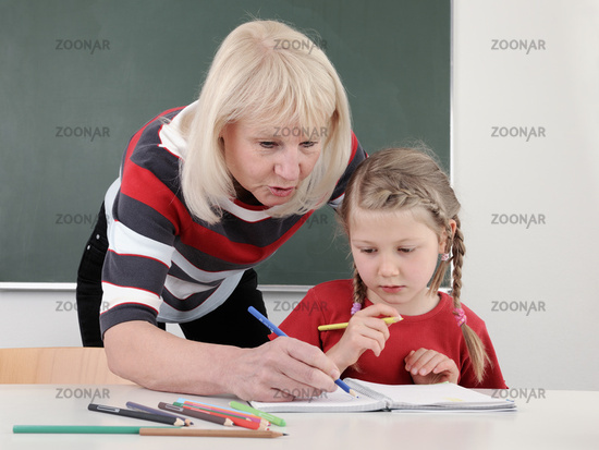 Teacher helping pupil with reading