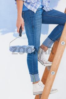 Woman holding paint roller climbing ladder