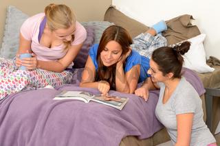 Three teenage girls reading at slumber party