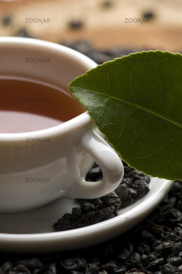 A cup of green tea with freh leaves