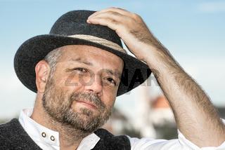 Man holding his Bavarian black hat