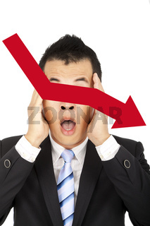 depressed businessman watching the red graph decreasing