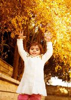 Small girl in autumn backyard