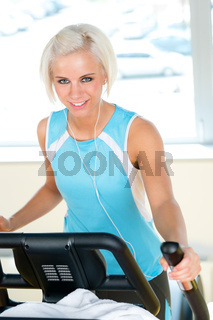 Fitness young woman on elliptical cross trainer