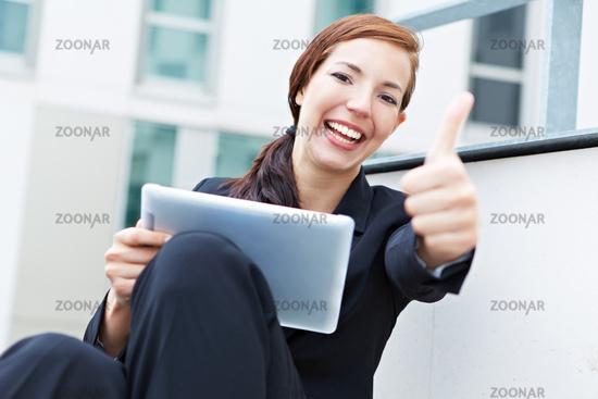 Frau mit Tablet Computer hält Daumen hoch