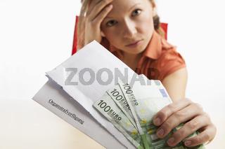 Junge Frau hällt Organstrafverfügung und Geld in der Hand