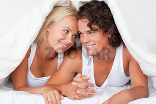 Portrait of an in love couple under a duvet