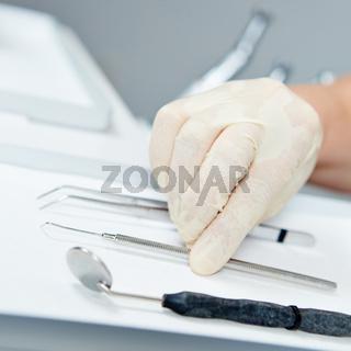 Zahnarzt greift mit Hand nach Sonde