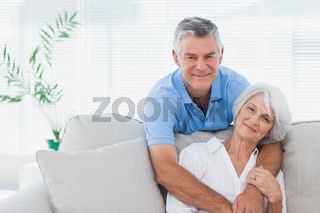 Man embracing wife who is sitting on the couch