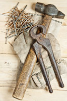 Vintage hammer with nails on wood background