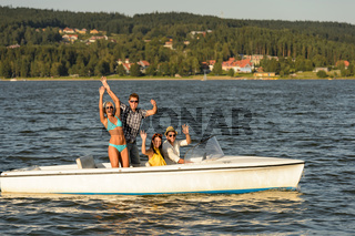 Young friends enjoying summer on speed boat