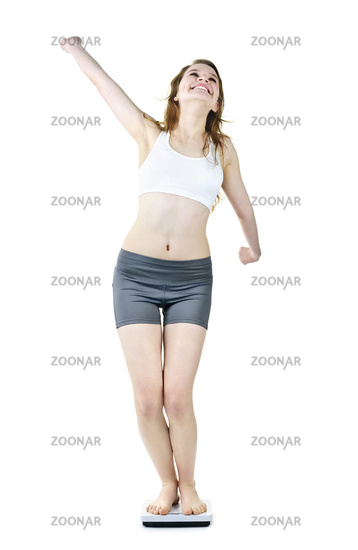 Excited fit young girl on bathroom scale