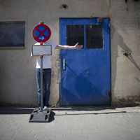 Young Man behind a road sign