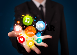 Young businessman presenting colorful technology icons and symbols