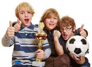 Jungs mit Pokal und Fußball halten Daumen hoch