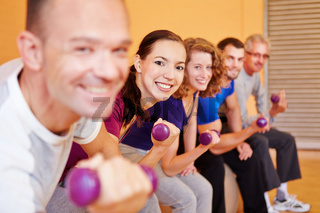 Gruppe hebt Hanteln beim Fitnesskurs