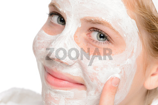 Young smiling girl applying cleaning facial mask