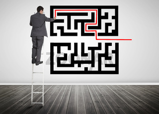 Businessman standing on a ladder drawing line through qr code
