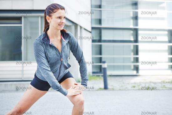 Fitte Frau dehnt sich vor dem Laufen