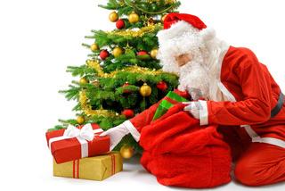 Weihnachtsmann legt Geschenke unter den Christbaum