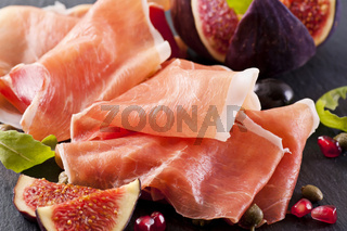 Prosciutto with figs on a black plate