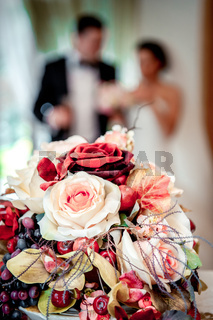 Beautiful bridal bouquet and bride and groom on background, selective focus