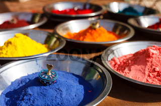 India symbol. Colored colorful powder kumkum in bowls on Indian bazaar for Holi and other festivals celebration