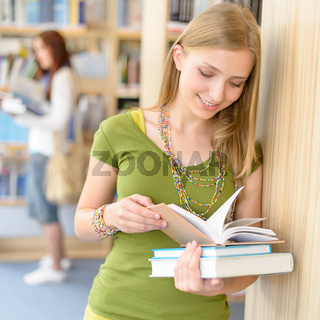 Teenage student with book at high school library